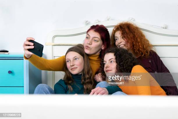 mother and her three daughters sitting together on bed taking selfie with smartphone - four people stock pictures, royalty-free photos & images