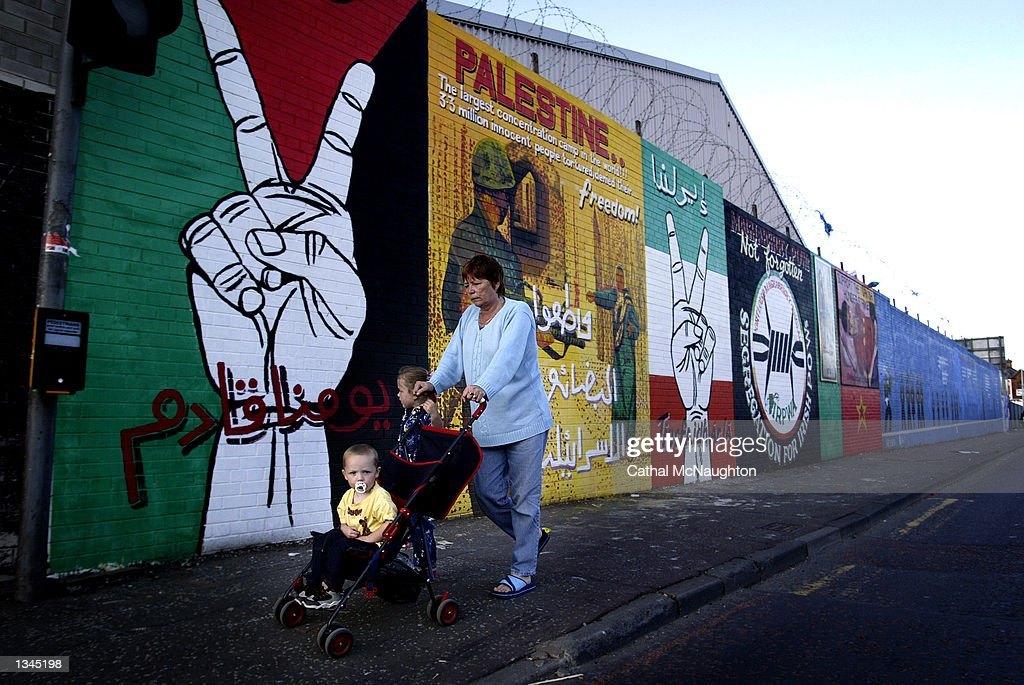 A mother and her two children pass by a mural on Falls Road August 20, 2002 in west Belfast, Northern Ireland. The pro-Palestinian painting has appeared in several Nationalist areas across Belfast in recent weeks.