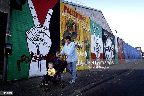 Mother and her two children pass by a mural on Falls Road August 20, 2002 in west Belfast, Northern Ireland. The pro-Palestinian painting has...