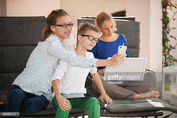 Mother and her two children relaxing with digital tablet, smartphone and laptop on the terrace