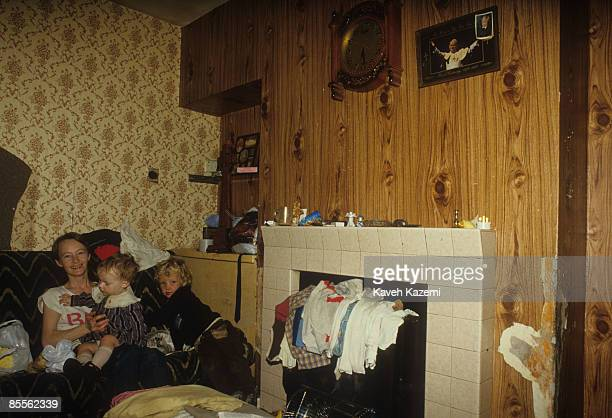 A mother and her two children sit on the sofa of their the living room in the Catholic residential area of west Belfast 18th September 1985 A picture...