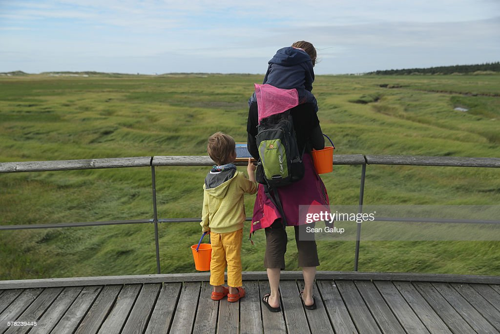 A mother and her two children stand on a wooden walkway that crosses protected dunes and salt marshes on July 18, 2016 at Sankt-Peter-Ording, Germany. Sankt-Peter-Ording is among the top destinations for vacationers along Germany's North Sea coast. Many Germans, unsettled by the recent terror attacks in countries like France and Turkey, are choosing to vacation in Germany this summer.