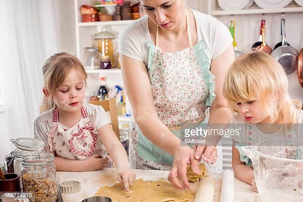 Mutter und ihre zwei Töchtern in der Küche vorbereiten Kekse