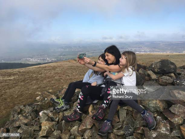 mother and her two daughters taking a selfie on the summit of dent fell - whitehaven cumbria stock pictures, royalty-free photos & images