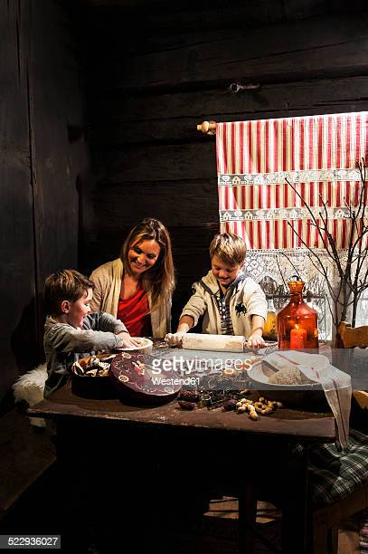 Mother and her two little sons  baking Christmas cookies at Advent Season