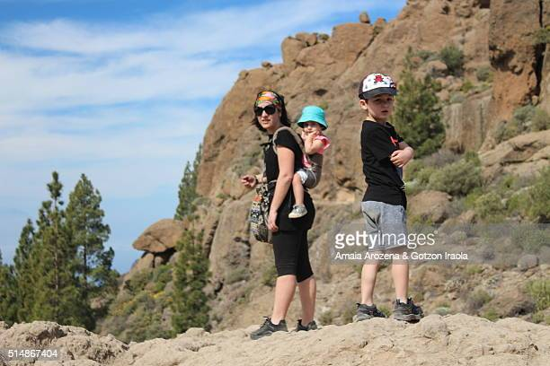 Mother and her two small kids hiking to the Roque Nublo of Grand Canary