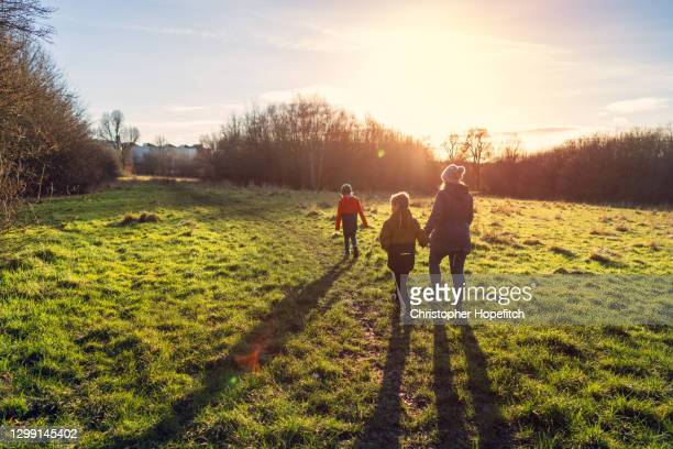 a mother and her two young sons walking in a country park in low winter sunlight - europe stock pictures, royalty-free photos & images