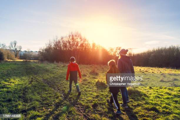 a mother and her two young sons walking in a park near sunset - winter stock pictures, royalty-free photos & images