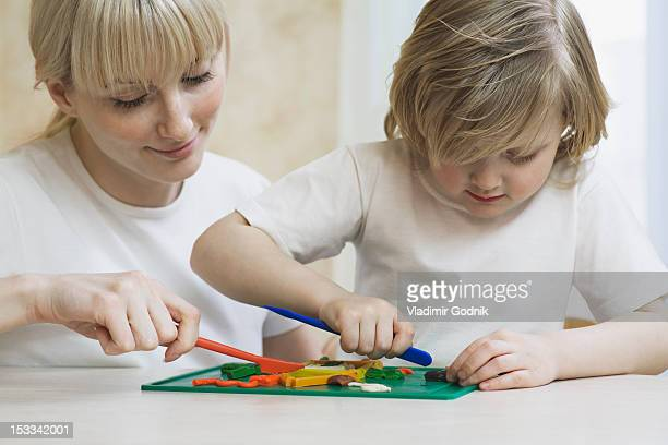 A mother and her young daughter playing with child's play clay