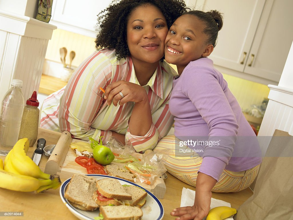 Mother and Her Young Daughter Sit at a Kitchen Table With a Plate of Sandwiches, Cheek to Cheek, Smiling : Stock Photo