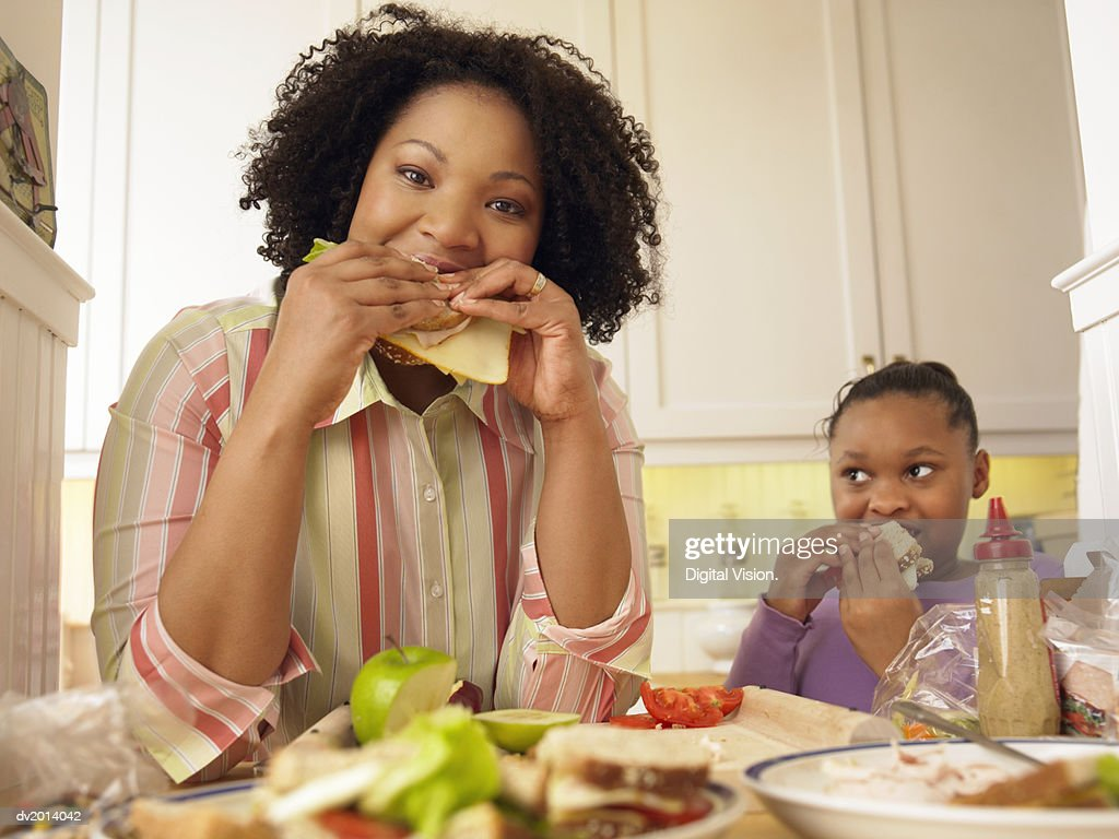 Mother and Her Young Daughter Stand in the Kitchen Eating Cheese Sandwiches for Lunch : Stock Photo