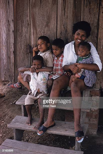 A mother and her young family sit on their steps in New Orleans Louisiana