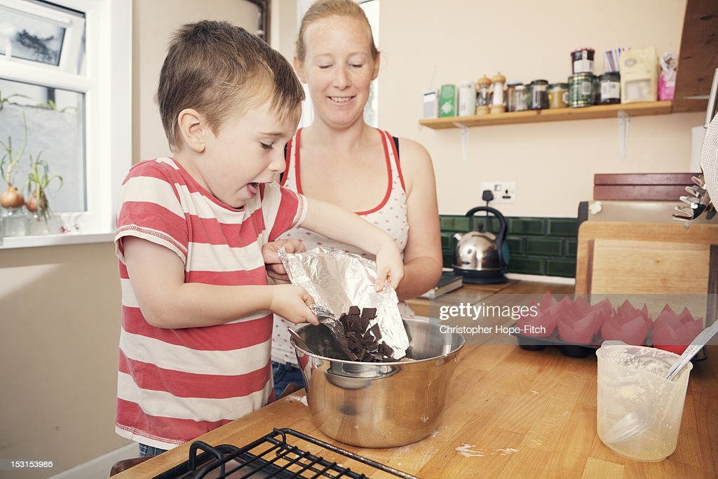 Mother and her young son baking some chocolate muffins in their kitchen at home.