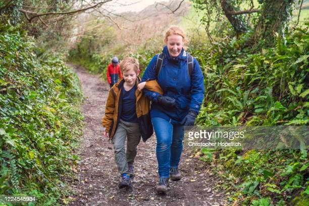 a mother and her young son walking up a steep path in the countryside - mid adult stock pictures, royalty-free photos & images