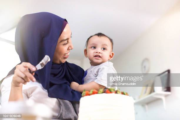 A mother and home baker bonding with baby while decorating a cake