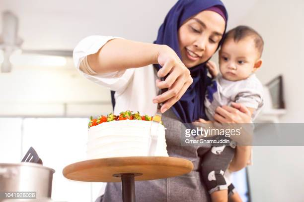 A mother and home baker decorating a cake while holding a baby