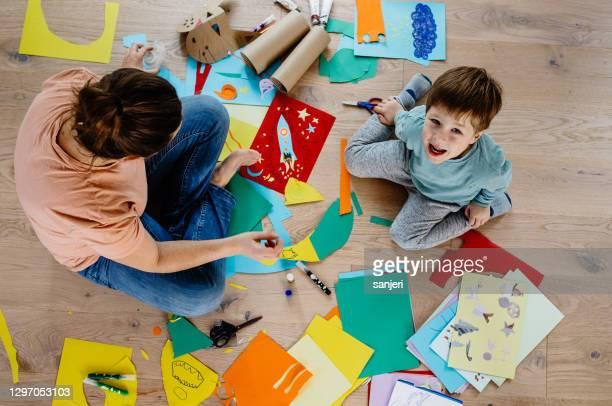 madre e hijo cortando papel y haciendo collages - fotografía producto de arte y artesanía fotografías e imágenes de stock