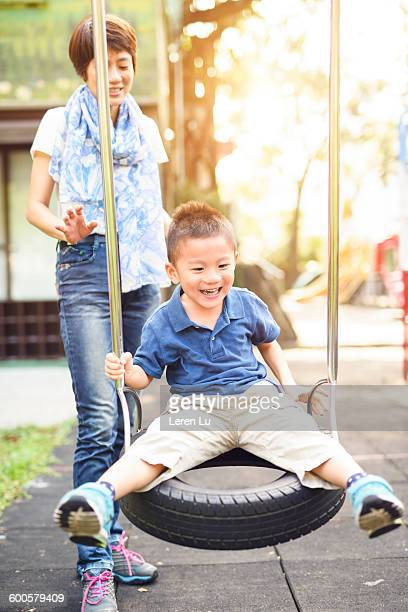 Mother and kid playing swing