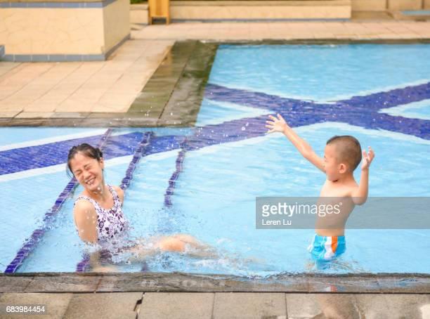 Mother and kid splashing in swimming pool
