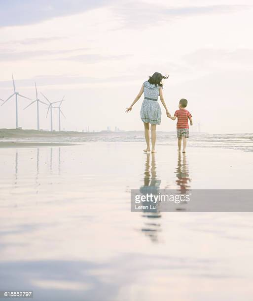 Mother and kid walking on beach