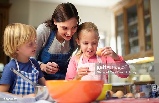 Mother and kids baking a cake