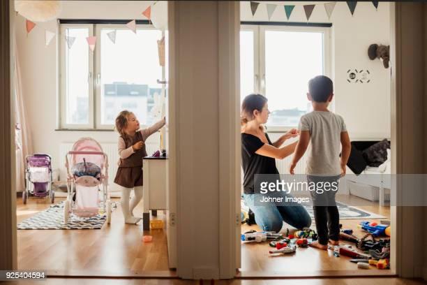 mother and kids cleaning house - haushaltsaufgabe stock-fotos und bilder