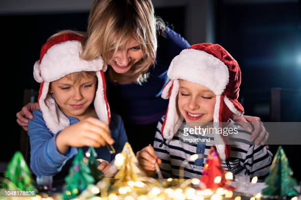 mother and kids crafting christmas decorations - santa hat stock photos and pictures
