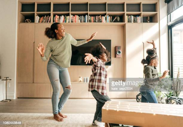 mother and kids dancing - african american family home stock photos and pictures