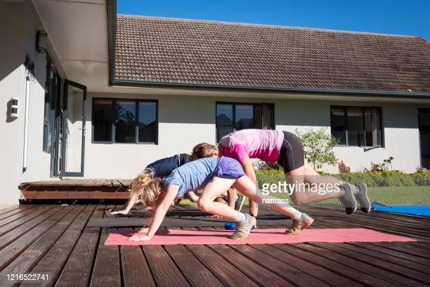 mother and kids doing a home workout outdoors - sibling stock pictures, royalty-free photos & images
