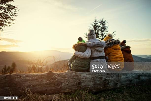 mother and kids enjoying sunset in mountains - winter stock pictures, royalty-free photos & images