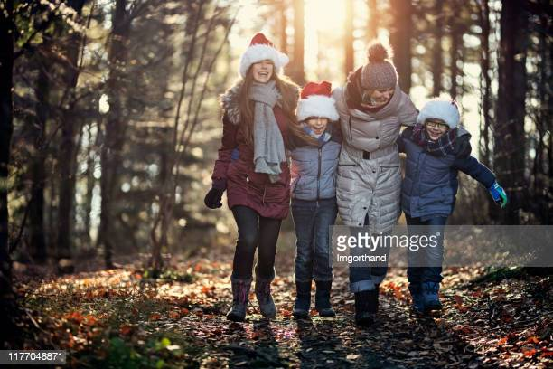 mother and kids enjoying walk in forest. - christmas family stock pictures, royalty-free photos & images