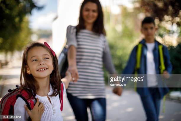 mother and kids going home from school - school building stock pictures, royalty-free photos & images