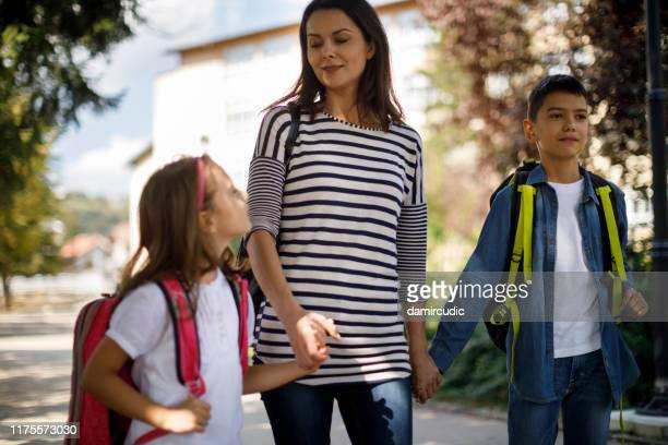 mother and kids going home from school - damircudic stock photos and pictures