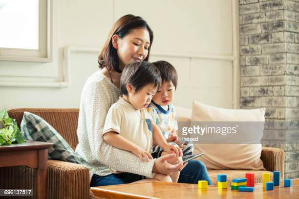 Mother and kids looking at smart phone on sofa