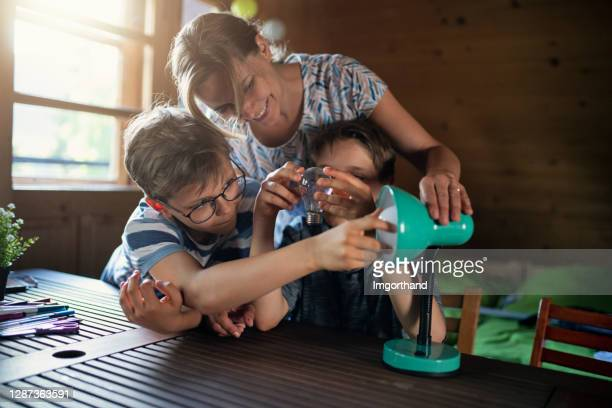 mother and kids saving energy by changing bulbs - energy efficient stock pictures, royalty-free photos & images