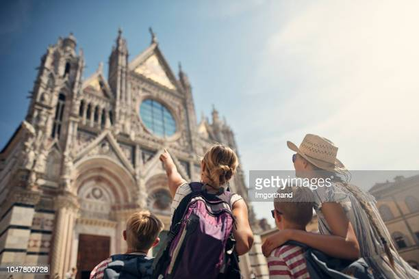 mother and kids sightseeing city of siena, tuscany, italy - turista foto e immagini stock
