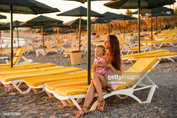 Mother and litle daughter at sunset on the beach.