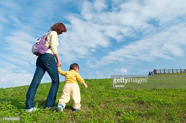 Mother and little boy climbing hill