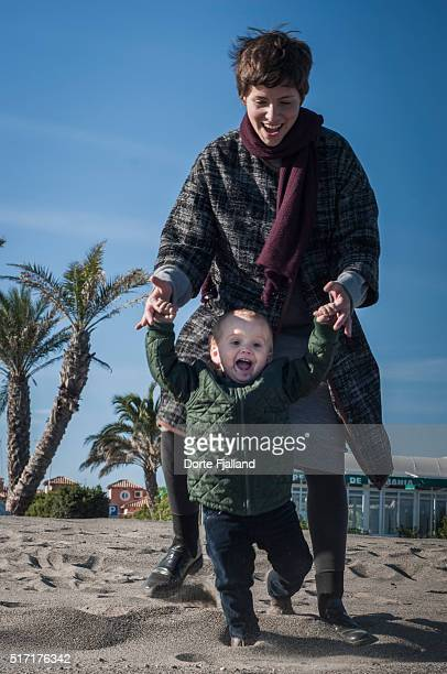 Mother and little boy jumping on a beach