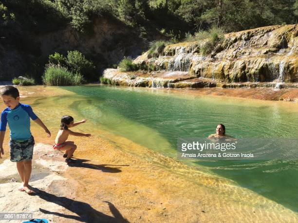 Mother and little children in Samper Bajo natural pools in Paternoy ravine. Huesca province. Spain.