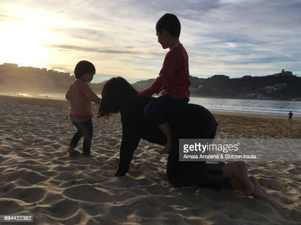 Mother and little children playing in La Concha beach. Donostia-San Sebastian, Basque Country