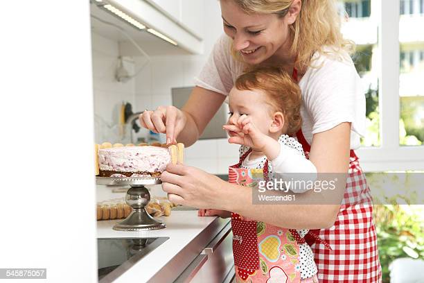Mother and little daughter baking cake together in their kitchen