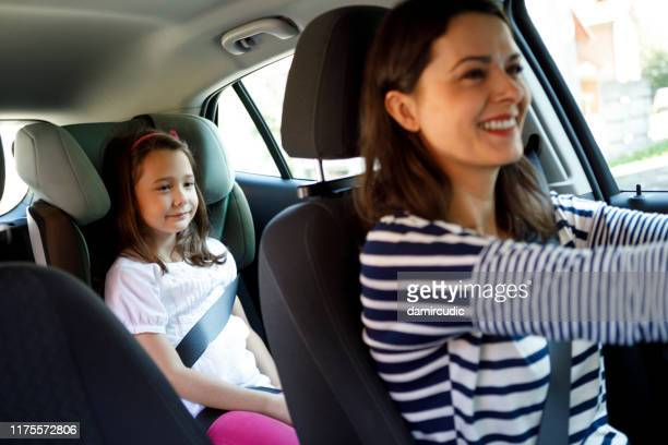 mother and little daughter driving in car together - damircudic stock photos and pictures