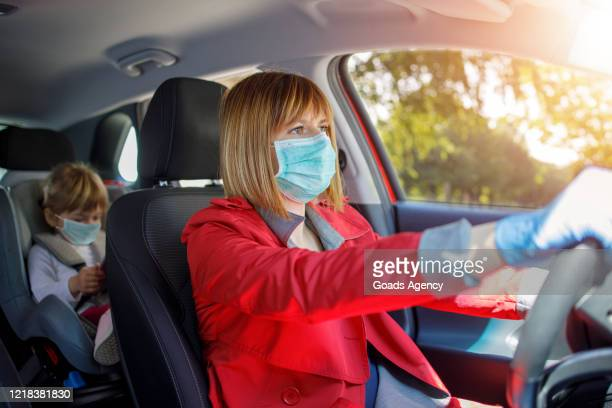 mother and little daughter driving in car together - driving mask stock pictures, royalty-free photos & images