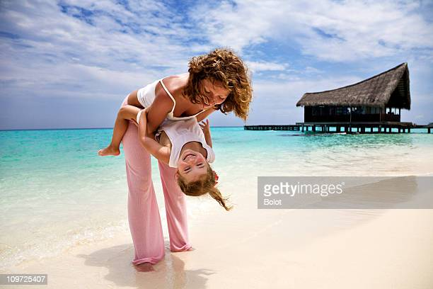 Mother and Little Daughter Having Fun on Tropical Beach