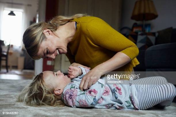 mother and little daughter having fun together at home - kitzeln stock-fotos und bilder