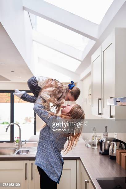 Mother and little daughter having fun together in the kitchen