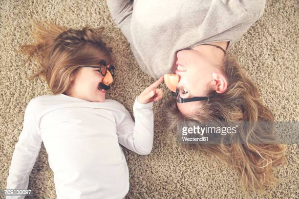 Mother and little daughter lying on the carpet having fun with comedy glasses