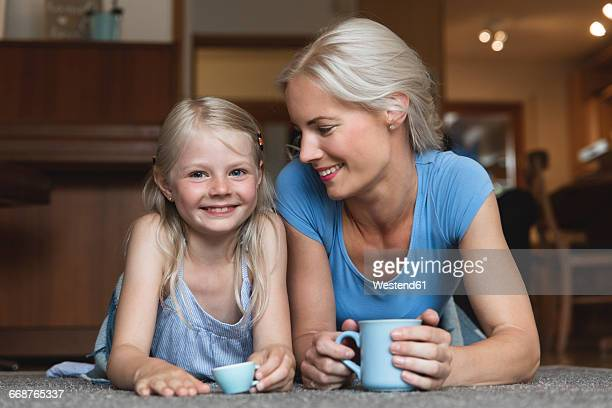 Mother and little daughter lying side by side on the floor holding cups