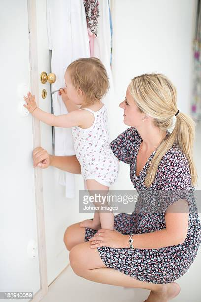 Mother and little daughter opening door with key